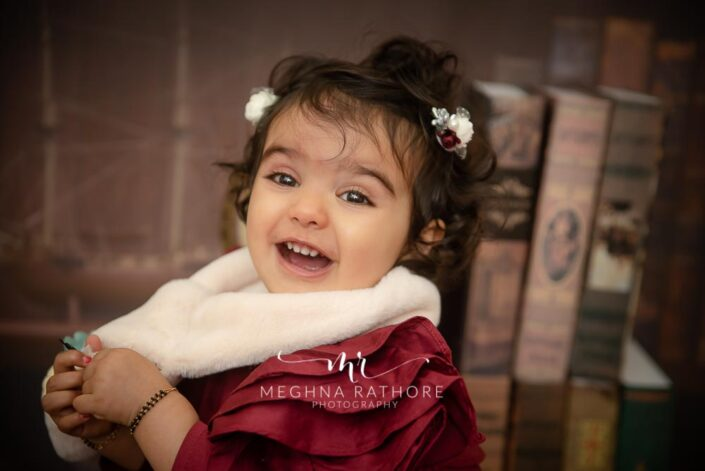 1 year old baby girl posing smiling brightly with theme and props at meghna rathore photography in delhi gurgaon