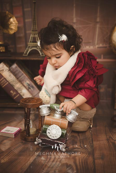 1 year old baby girl posing with theme and props like old telephone at meghna rathore photography in delhi gurgaon