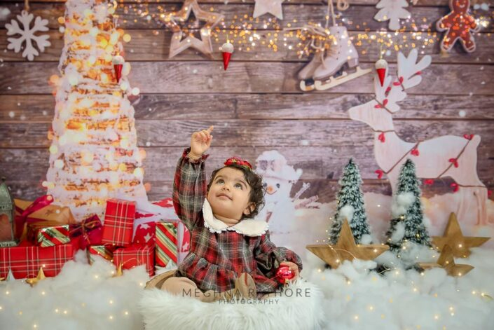 1 year old girl posing pointing upwards in a christmas themed professional photoshoot at meghna rathore photography in delhi gurgaon