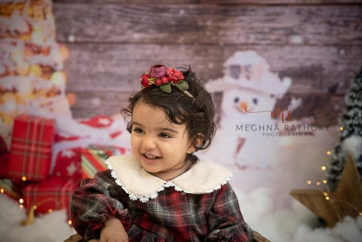 1 year old girl posing in a christmas themed professional photoshoot at meghna rathore photography in delhi gurgaon