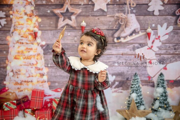 1 year old girl posing in a christmas themed professional holding a star in her hand photoshoot at meghna rathore photography in delhi gurgaon