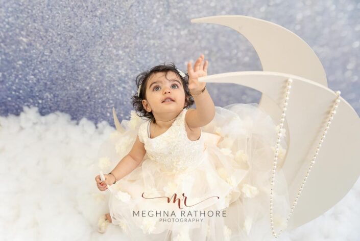 1 year old cute girl posing in moon themed professional photoshoot at meghna rathore photography in delhi gurgaon