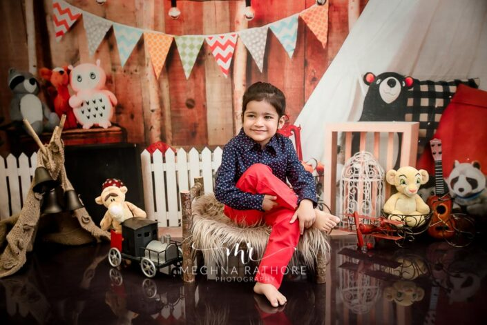 2 year old boy posing sitting with different props around him for professional photoshoot at meghna rathore photography in delhi gurgaon