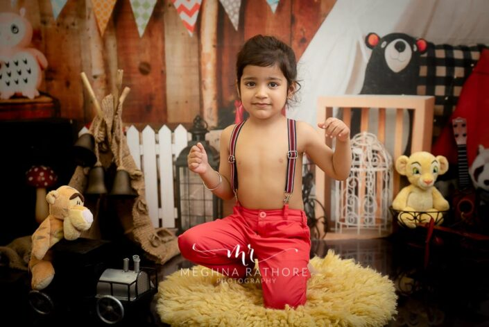 2 year cute old boy posing with different props and toys around him for professional photoshoot at meghna rathore photography in delhi gurgaon