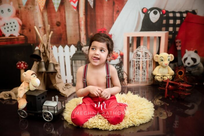 2 year old boy posing with different props and toys around him for professional photoshoot at meghna rathore photography in delhi gurgaon