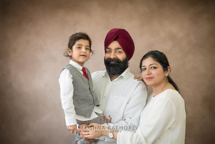 Cute family portrait of 2 year old boy with his parents posing at meghna rathore photography in delhi gurgaon