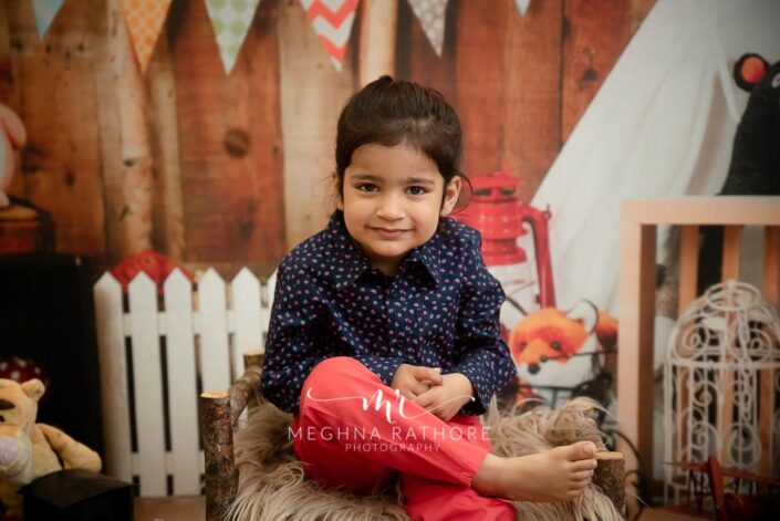 Adorable 2 year old boy posing sitting with different props around him for professional photoshoot at meghna rathore photography in delhi gurgaon