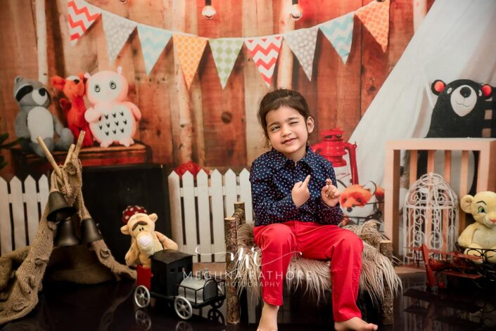 Cute 2 year old boy posing sitting with different props around him for professional photoshoot at meghna rathore photography in delhi gurgaon