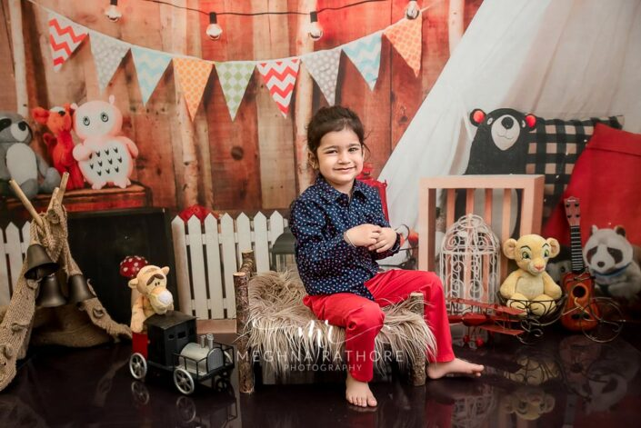 2 year old handsome boy posing sitting with different props around him for professional photoshoot at meghna rathore photography in delhi gurgaon