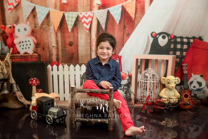 2 year cute old boy posing sitting with different props around him for professional photoshoot at meghna rathore photography in delhi gurgaon