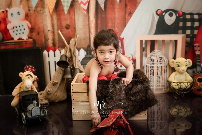 2 year cute old boy posing inside a wooden box with different props around him for professional photoshoot at meghna rathore photography in delhi gurgaon