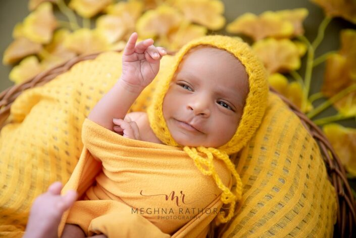 21 days old newborn baby boy photoshoot in yellow colored themed props at meghna rathore photography in delhi gurgaon
