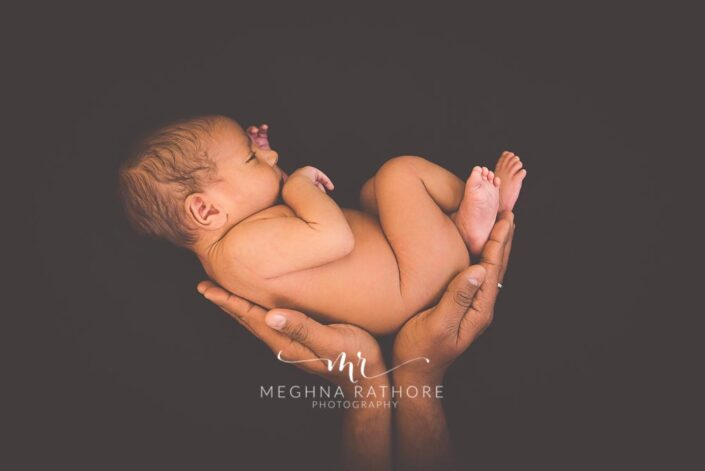21 days old newborn baby boy held up high by his father and posing at meghna rathore photography in gurgaon delhi