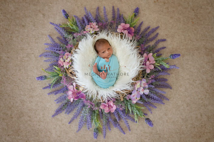 newborn baby boy tucked in a basket surrounded with flowers and leaves and posing at meghna rathore photography in delhi