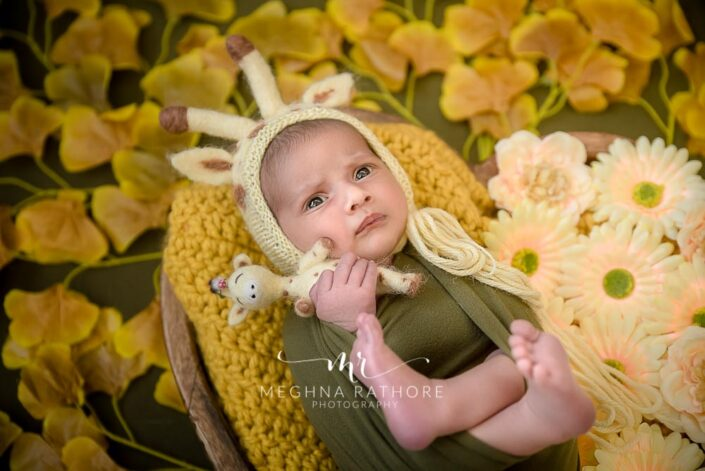 23 year old newborn baby tucked in green cloth surrounded with different props posing at meghna rathore photography in delhi