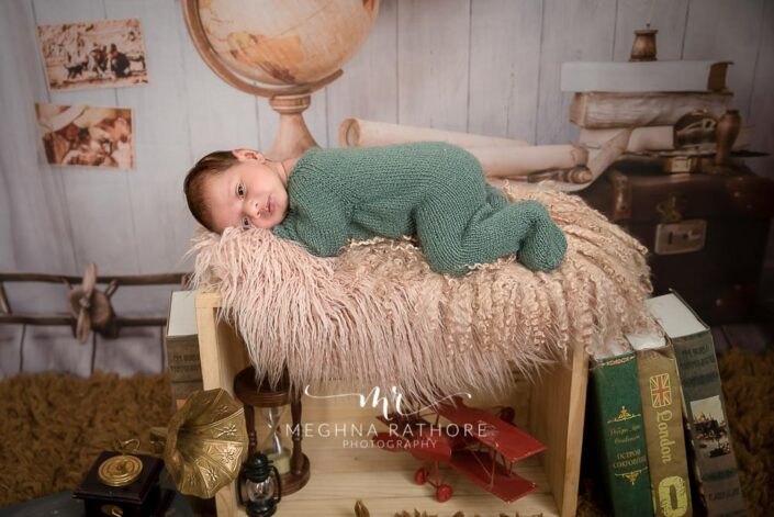 23 days old newborn baby in green colored woolen cloth and around different props at meghna rathore photography at delhi