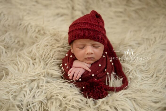 23 days old baby boy wrapped in red cloth and surrounded by white furry blanket at meghna rathore photography in delhi