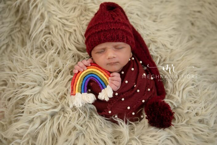 23 days old baby boy holding a rainbow woven toy in hand and posing at meghna rathore photography at delhi