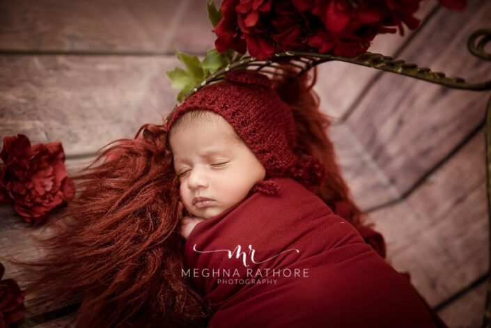 23 days old newborn baby boy with red colored theme and props at meghna rathore photography in delhi