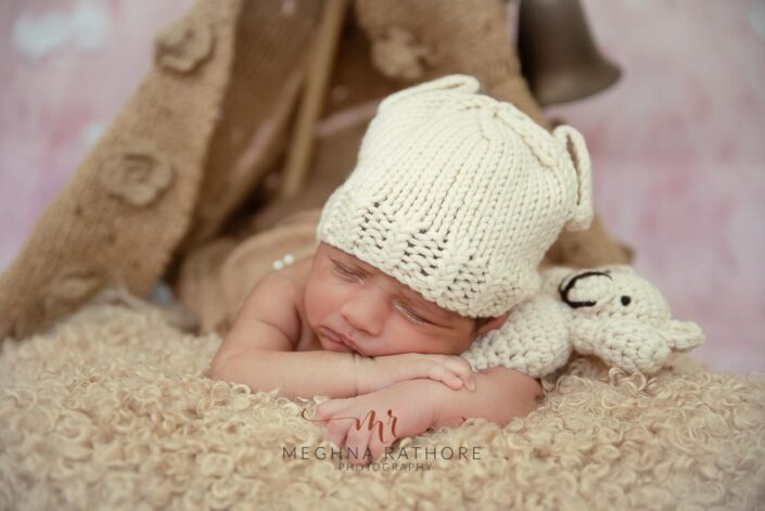 23 days old newborn baby boy with a white woolen cap and a toy beside with other props at meghna rathore photography in delhi