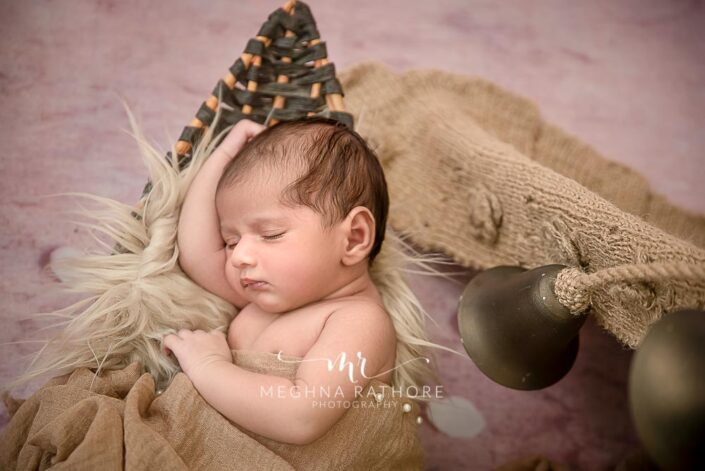 Newborn baby boy peaceful sleeping pose with props around hi at meghna rathore photography in delhi