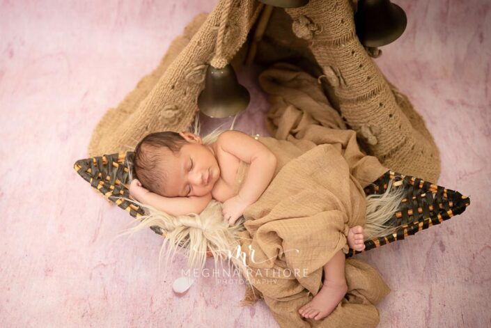 23 days old baby boy in a brown colored props around him at meghna rathore photography in delhi