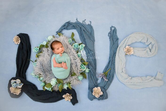 Newborn baby boy posing with the word 'LOVE' written decorated with clothes and posing at meghna rathore photography in delhi