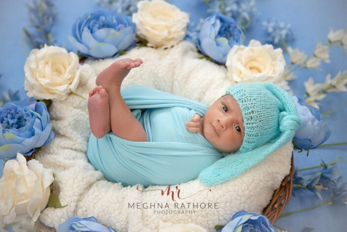 23 days old newborn baby boy tucked in a white blanket covered basket with white and blue flowers around him and posing at meghna rathore photography in delhi