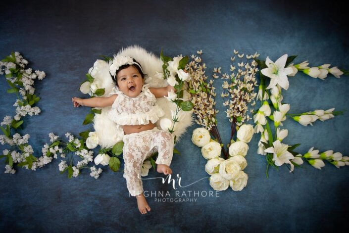"""4 months old baby girl posing with flowers around her in the letters """"love"""" professional photoshoot at meghna rathore photography"""