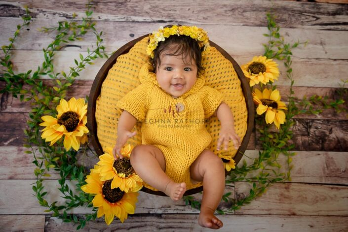 4 months old baby girl photoshoot with yellow colored sunflower theme and props posing at meghna rathore photography in delhi