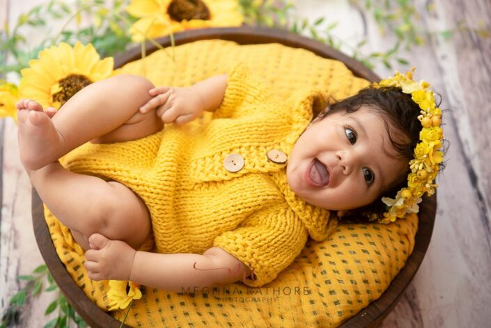 4 months old baby girl photoshoot with yellow colored theme and props posing at meghna rathore photography in delhi