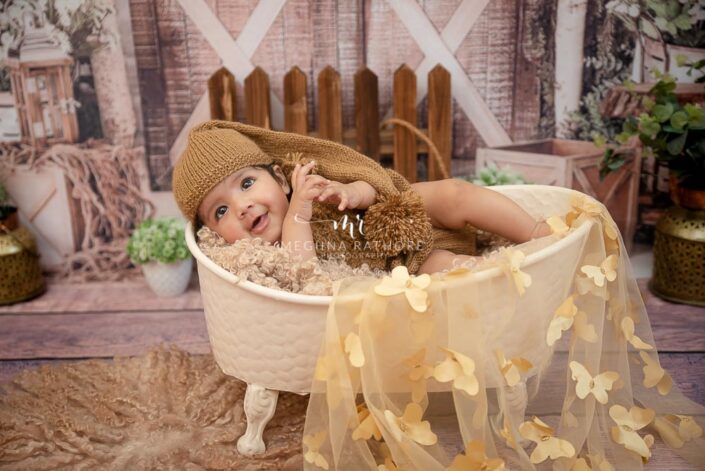 4 months old baby girl in small bath tub and props around her at meghna rathore photography in delhi