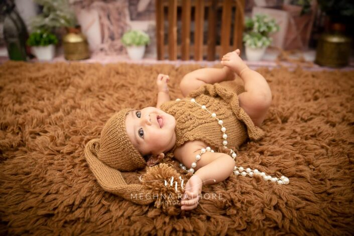 4 months old baby girl posing in brown colored props and clothes at meghna rathore photography in delhi