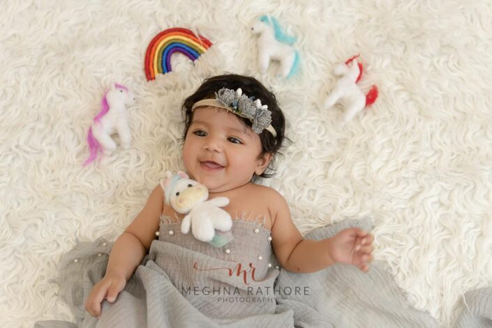 4 months old baby girl professional photoshoot with props like unicorn toys and rainbow at meghna rathore photography in delhi