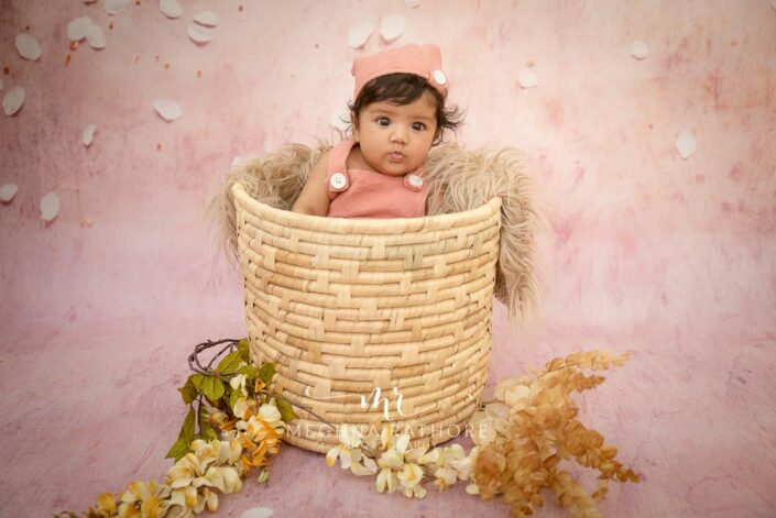 4 months old baby girl in a big basket with props like flowers and leaves posing at meghna rathore photography in delhi