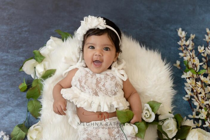 4 months old baby girl posing flowers around her professional photoshoot at meghna rathore photography