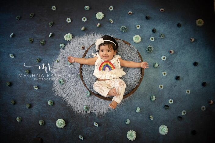 4 months old baby girl tucked in basket and flowers around her professional photoshoot at meghna rathore photography