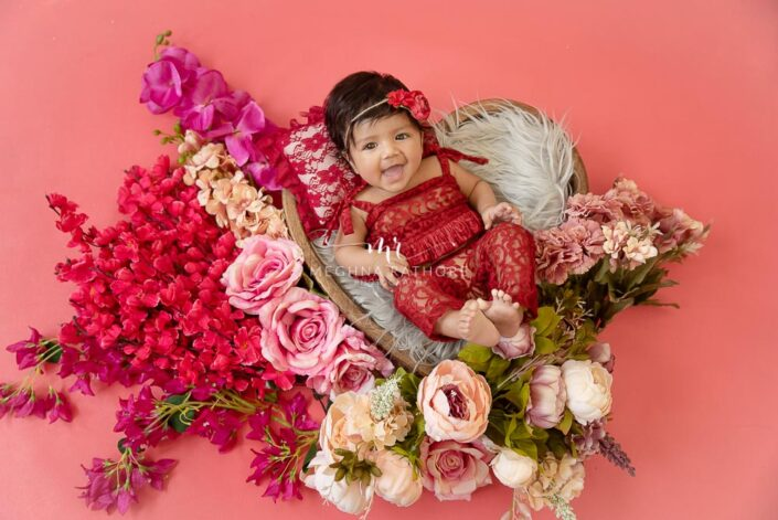 4 months old baby girl tucked in a heart shaped basket and flowers around her professional photoshoot at meghna rathore photography
