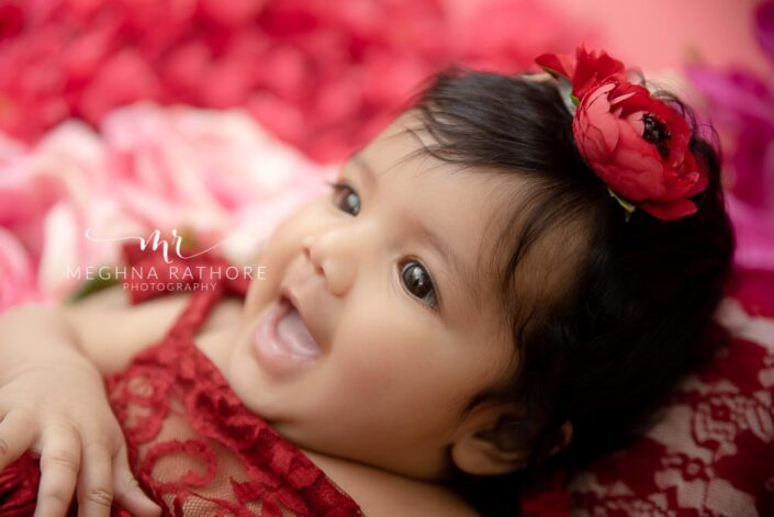 4 months old baby girl photoshoot with red colored rose theme and props posing at meghna rathore photography in delhi
