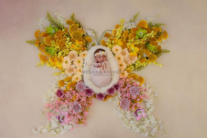 20 days old newborn baby girl tucked in basket in the center of butterfly pattern filled with flowers at meghna rathore photography in delhi