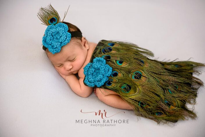 20 days old newborn baby girl sleeping and posing in a peacock outfit at meghna rathore photography