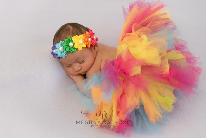 20 days old newborn baby girl in a colorful dress and tiara sleeping and posing at meghna rathore photography