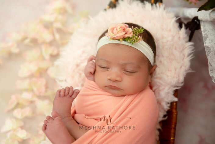 20 days old newborn baby girl posing inside a basket decorated with furry blanket and flowers around them at meghna rathore photography