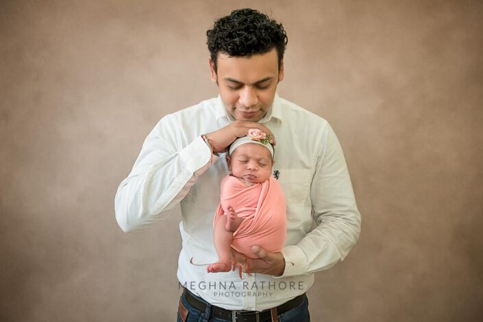 father and 20 days old newborn baby girl together posing for photoshoot at meghna rathore photography