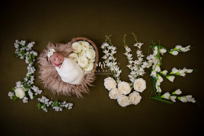 newborn baby girl - top angle shot of she tucked in a basket and the wrod love is decorated with flowers beside her- photoshoot at meghna rathore photography