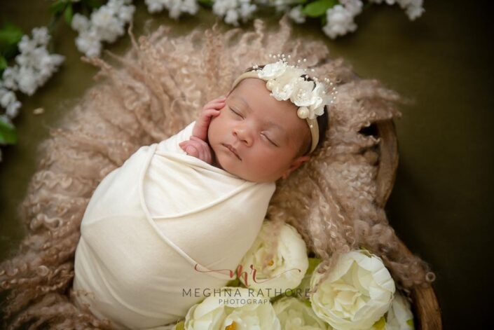 20 days old newborn baby girl -tucked in a basked with roses and white plain cloth a close up shot pose at meghna rathore photography delhi