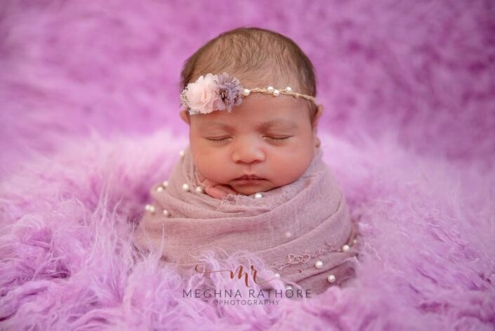 20 days old newborn baby girl with purple colored theme backdrop at meghna rathore photography in delhi