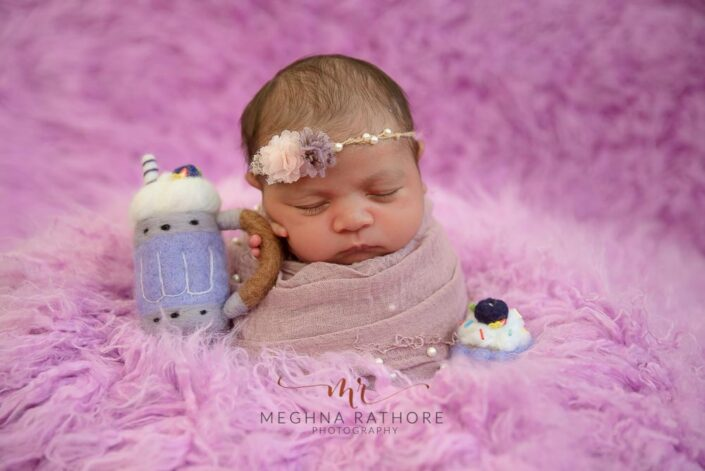 20 days old baby girl professional photoshoot with a purple backdrop and props at meghna rathore photography in delhi