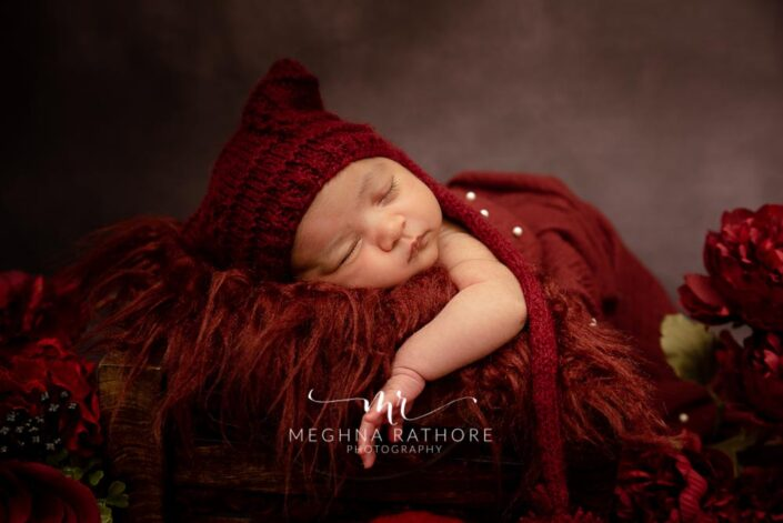 20 old days newborn baby girl professional with red colored theme props at meghna rathore photography in delhi