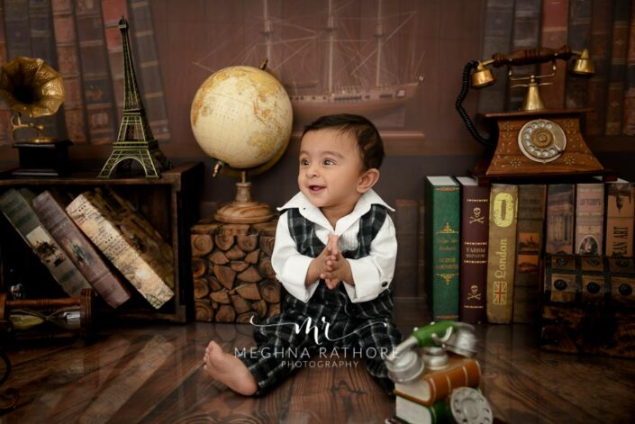 9 months old baby boy wearing black and white outfit sitting and posing with office theme based professional photoshoot at meghna rathore photography in noida